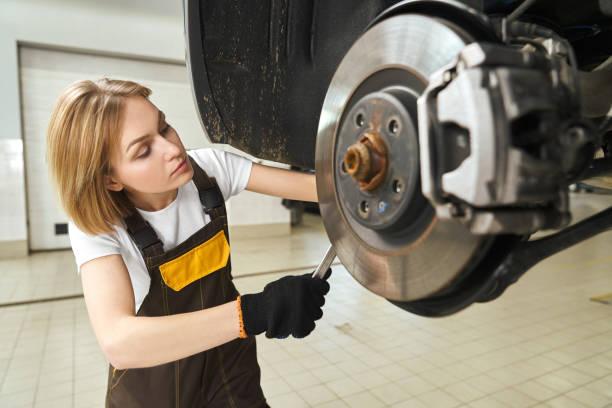 fille en combinaisons fixant le disque de frein de voiture, utilisant l'outil. - disque de frein photos et images de collection