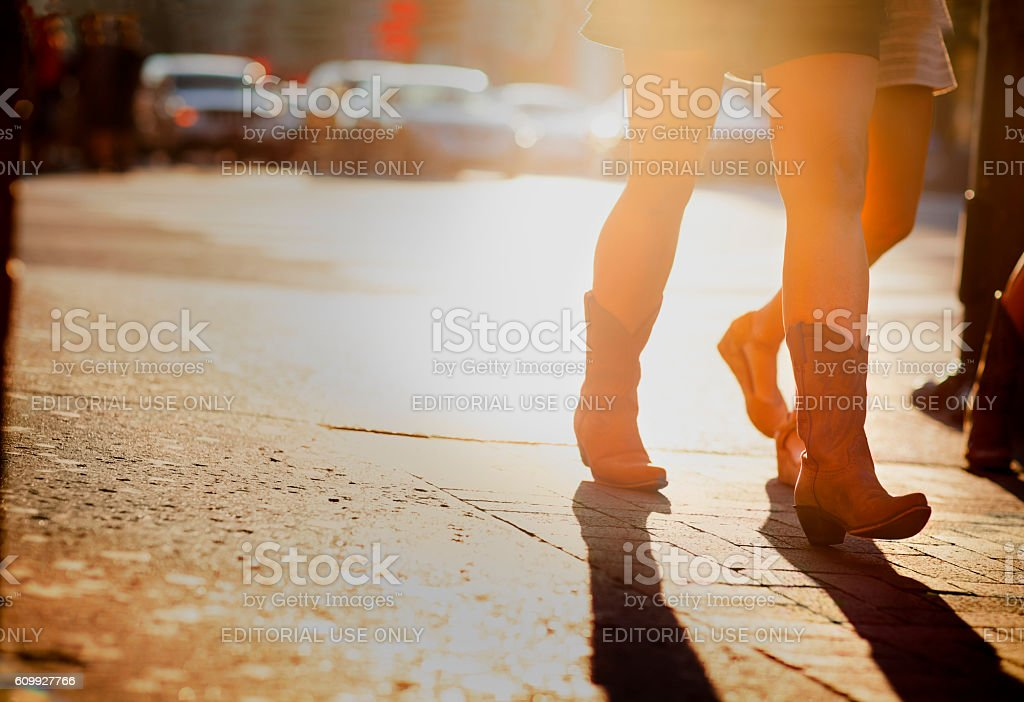 Girl in cowboy boots walking on Lower Broadway Street, Nashville Nashville, United States - September 23, 2016: Girl in cowboy boots walking on Lower Broadway street in downtown Nashville, Tennessee.  The district is famous for its country music entertainment and bars. American Culture Stock Photo