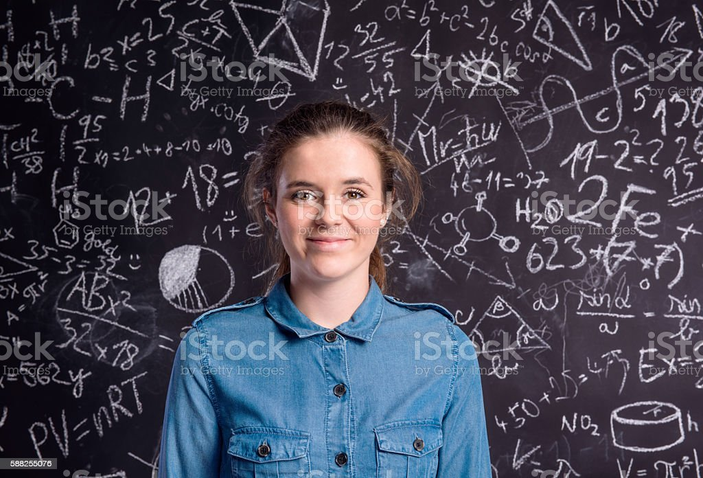 Girl in denim shirt against big blackboard with formulas stock photo