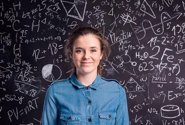 Girl in denim shirt against big blackboard with formulas - foto de acervo