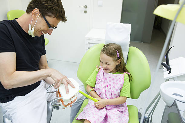 Girl in dentists chair tooth-brushing a model stock photo