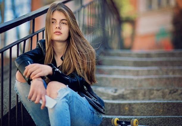 mädchen in depression steht traurig auf der treppe - bild wandtreppe stock-fotos und bilder