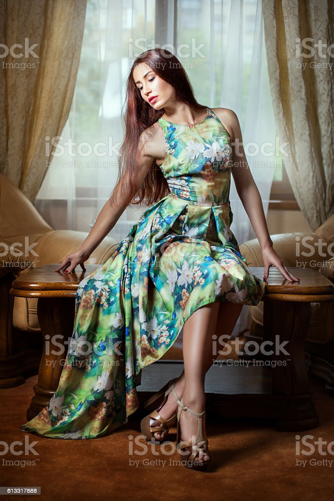 Girl in dress sitting in a room. stock photo