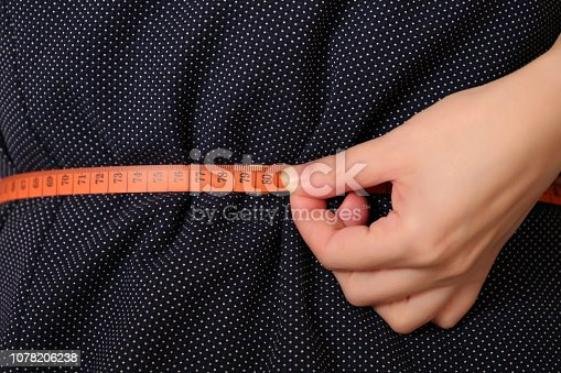 1163494373 istock photo Girl in dress with measuring tape around the waist 1078206238