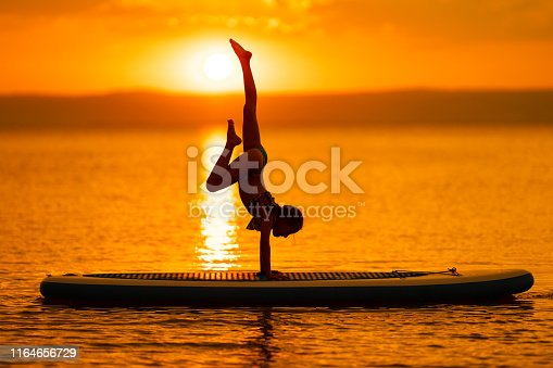 one 10 years old girl exercising sport gymnastics handstand sup board on lake summer vacations reflection water amazing sunset evening
