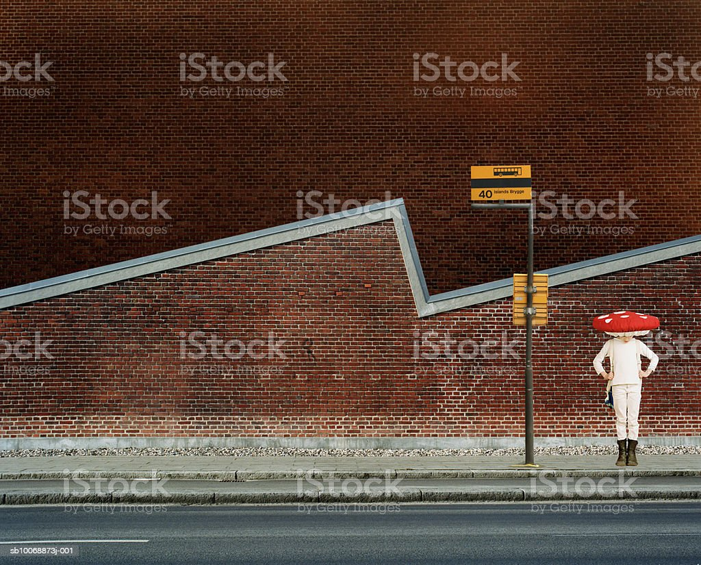 Girl (8-9) in fancy dress waiting for bus foto de stock libre de derechos