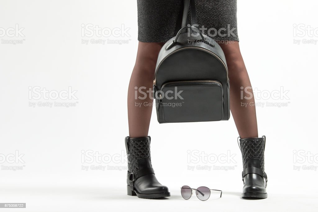 A girl in fashionable leather boots and a backpack in the studio stock photo