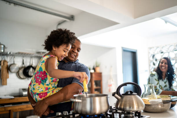 Girl in father's arms helping him cooking at home stock photo