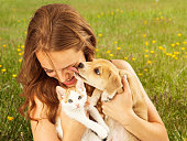 A cute young puppy licking the face of a pretty young girl as she is laughing