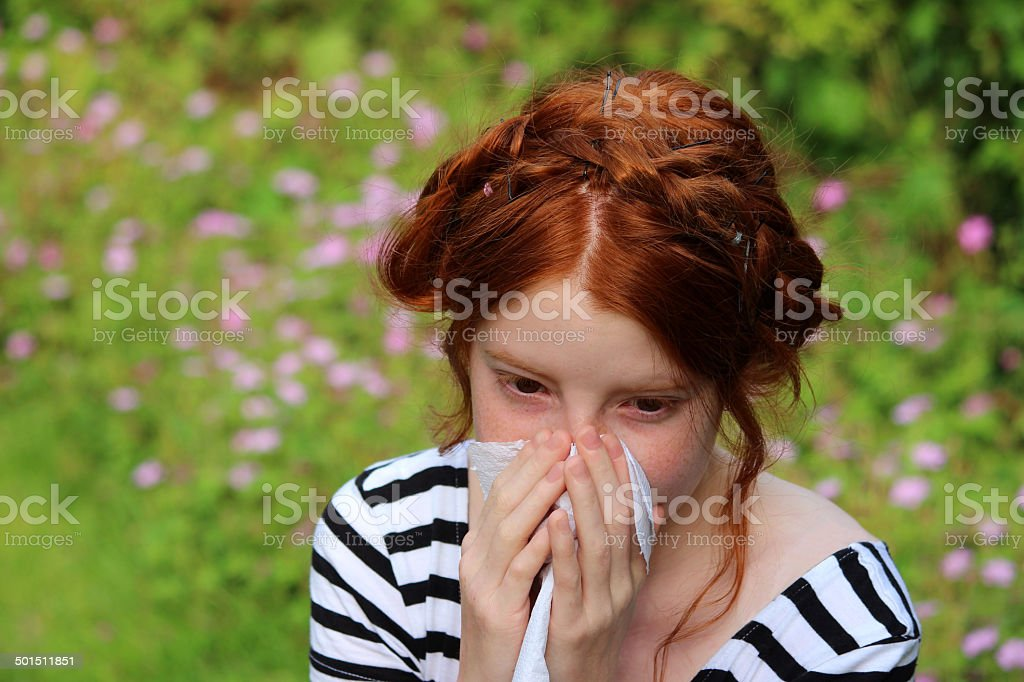 Photo showing a young girl sat in a garden on a sunny afternoon, with...