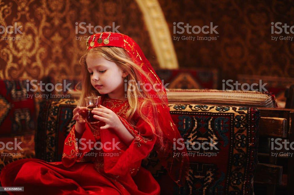 Girl in folk Arabic costume drinking Turkish tea stock photo