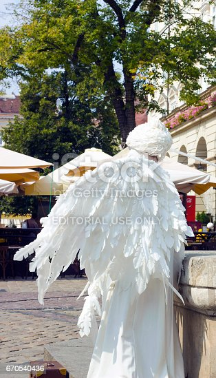 Girl in form of an angel in city. White live angel statue, side view
