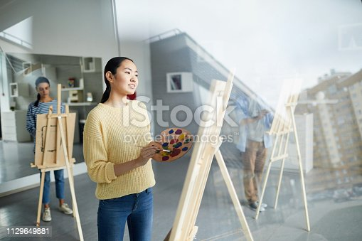824254912 istock photo Girl in front of easel 1129649881