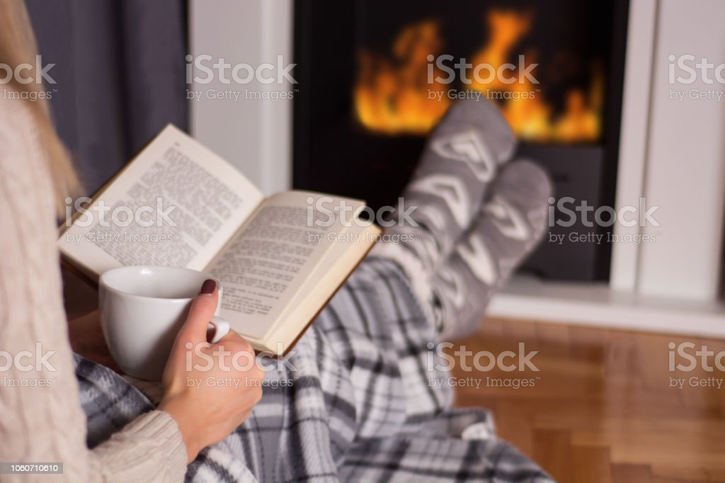 Beautiful young woman in front of the fireplace reading book and...