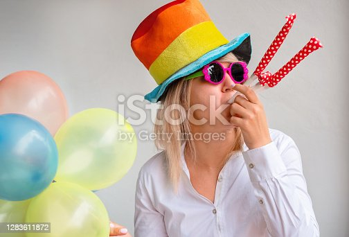 girl in a bright hat, sunglasses and balloons on a holiday