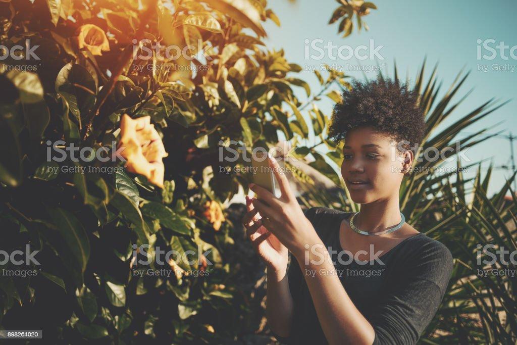 Mädchen im Garten nehmen Foto von Blütenknospe – Foto