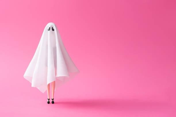 mädchen im geisterkostüm pastell rosa hintergrund. - cartoon kostüme stock-fotos und bilder