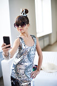Girl in glamour dress and sunglasses taking selfie