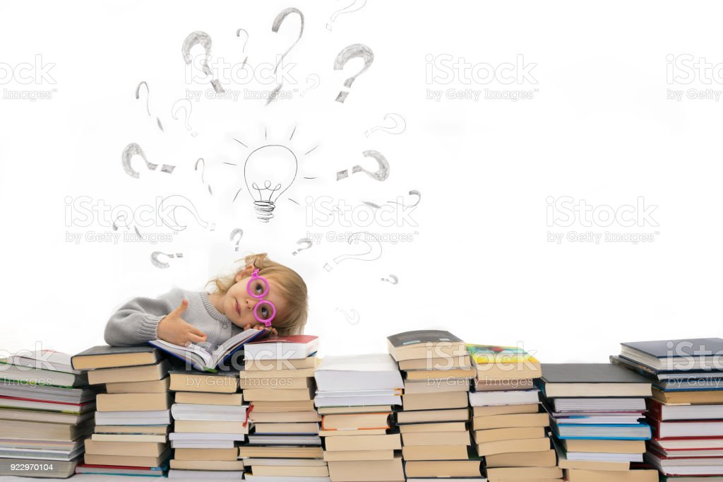 girl in glasses rests on books bulb and question mark stock photo