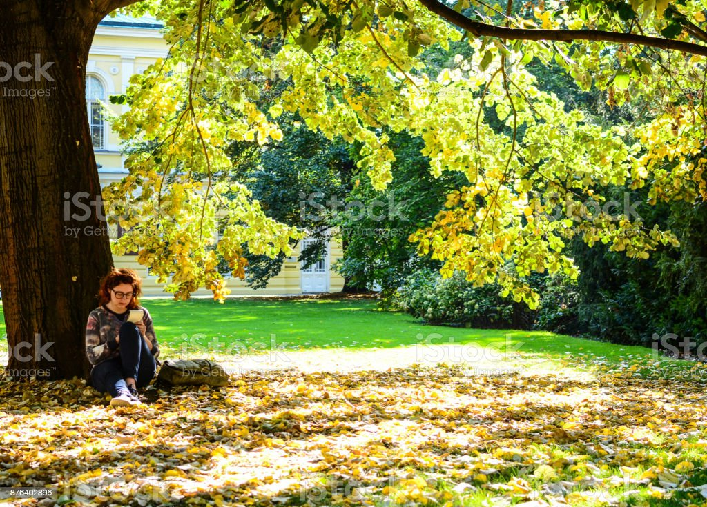 Girl in glasses with backpack sitting under the tree in autumn park and writing something in her notebook. Erasmus student, studying abroad and tourist concept stock photo