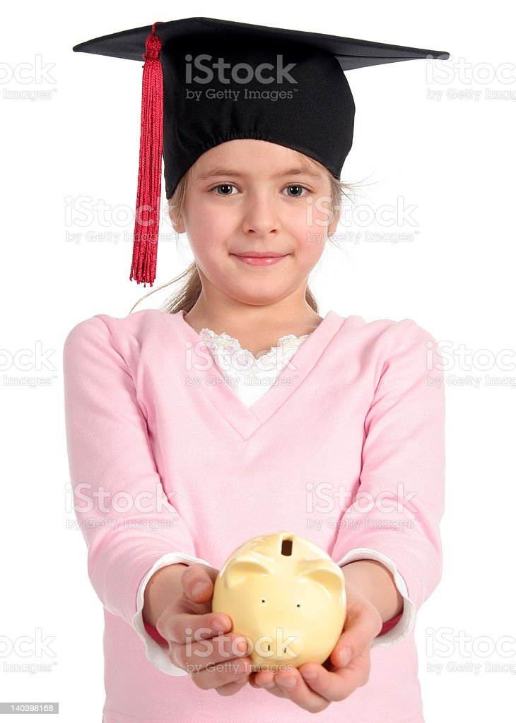 Girl in graduation cap holding piggy bank royalty-free stock photo