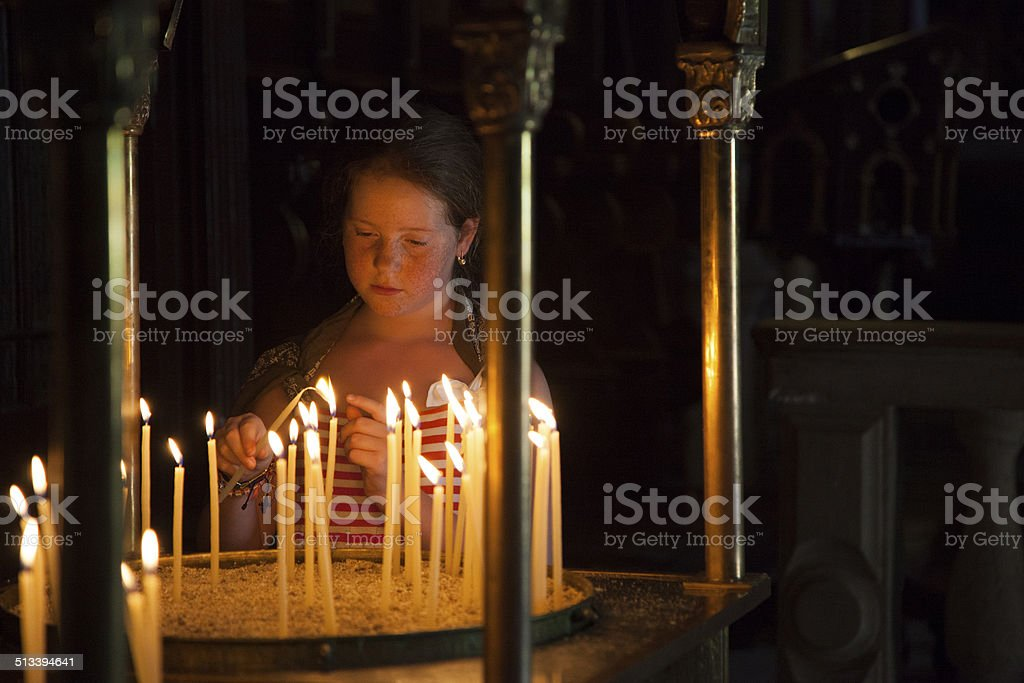 Girl in Greek orthodox church, lighting candles Girl in Greek orthodox church, lighting candles. 10-11 Years Stock Photo