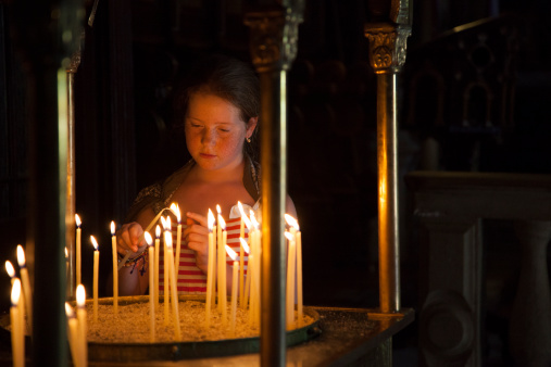 Girl In Greek Orthodox Church Lighting Candles Stock Photo - Download Image Now