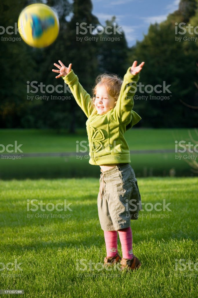 girl in green throwing a ball royalty-free stock photo