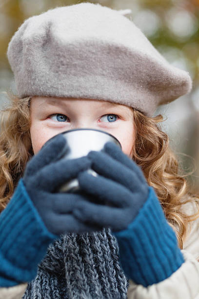Girl in grey beret drinking from flask cup stock photo