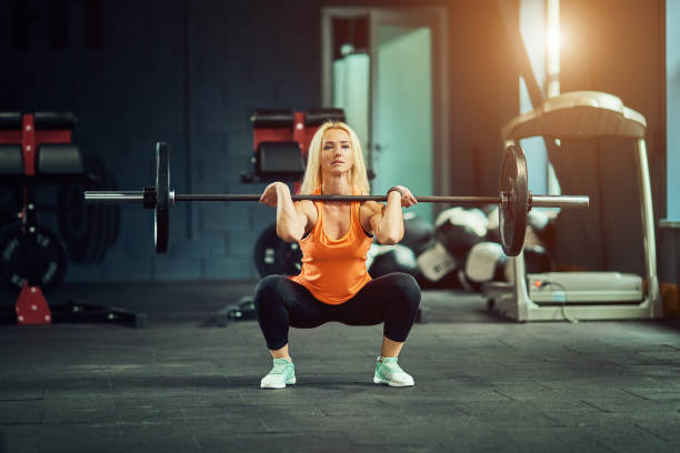 Girl in gym doing squats with barbell stock photo