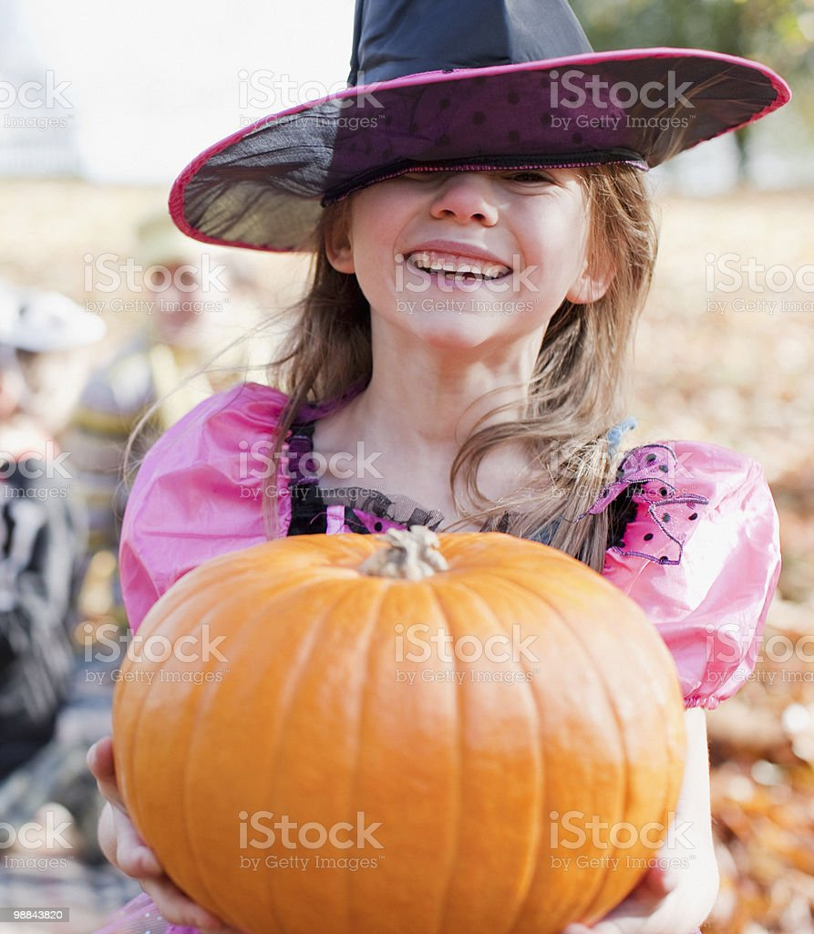 Girl in Halloween costume holding pumpkin royalty-free stock photo
