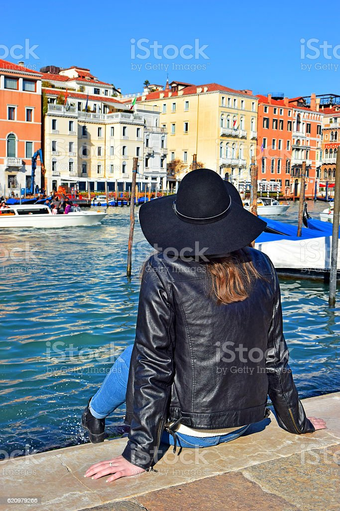 girl in hat sits on embankment of Grand Canal, Venice foto royalty-free