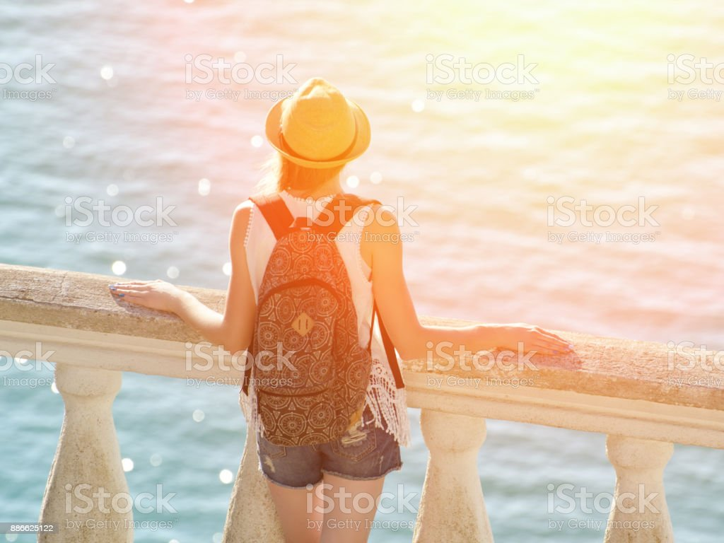 Girl in hat standing on the balcony and looking at the sea. View from the back stock photo