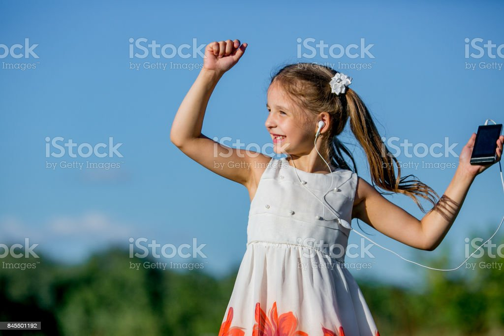 girl in headphones dancing to music in phone stock photo