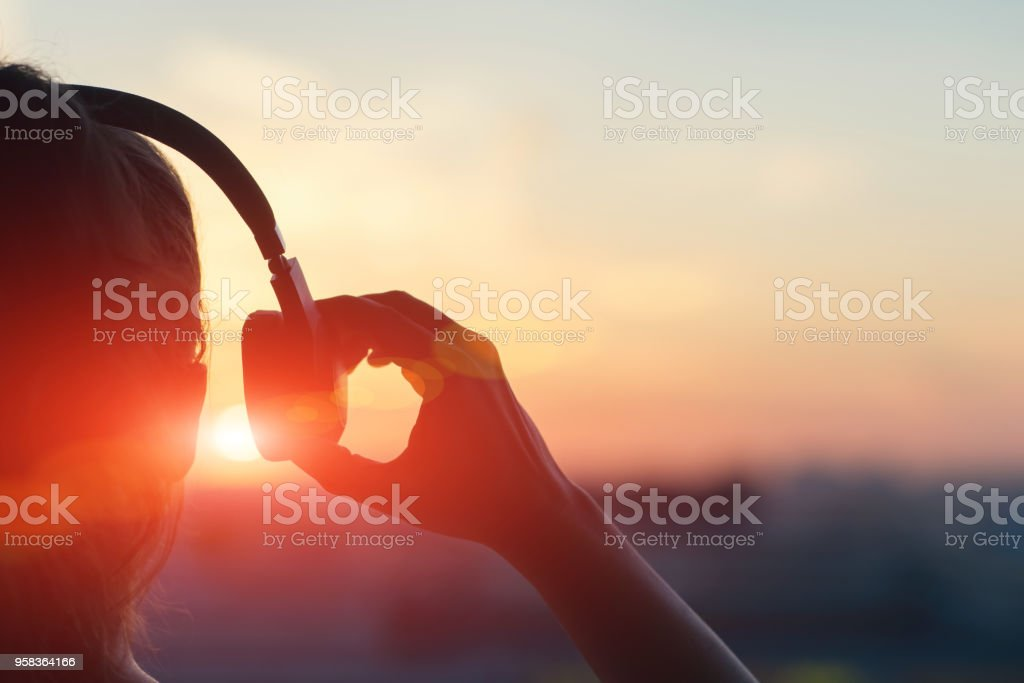 Fille au casque d'écoute de la musique dans la ville au coucher du soleil photo libre de droits