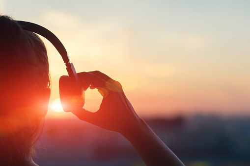 istock Girl in headphones listening to music in the city at sunset 958364166