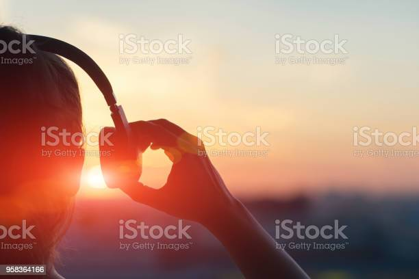 Girl In Headphones Listening To Music In The City At Sunset Stock Photo - Download Image Now
