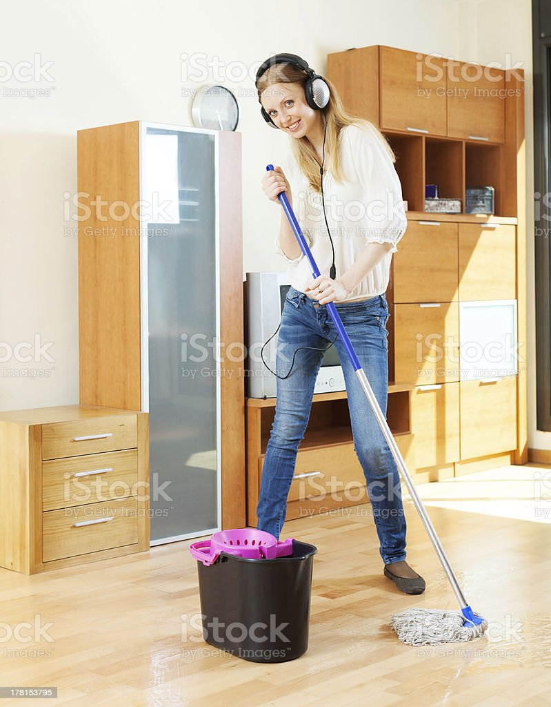 girl in headphones washing floor with mop royalty-free stock photo