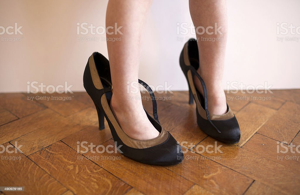 Girl in her mother's shoes stock photo