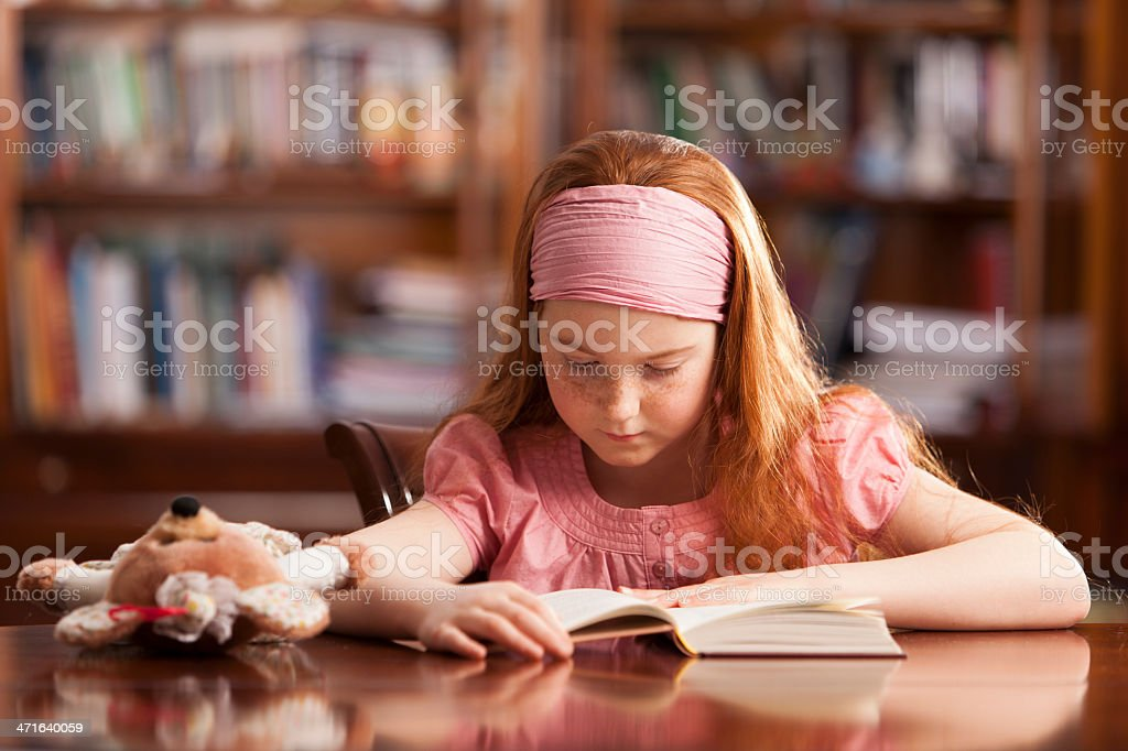 Girl in home setting, reading at table royalty-free stock photo