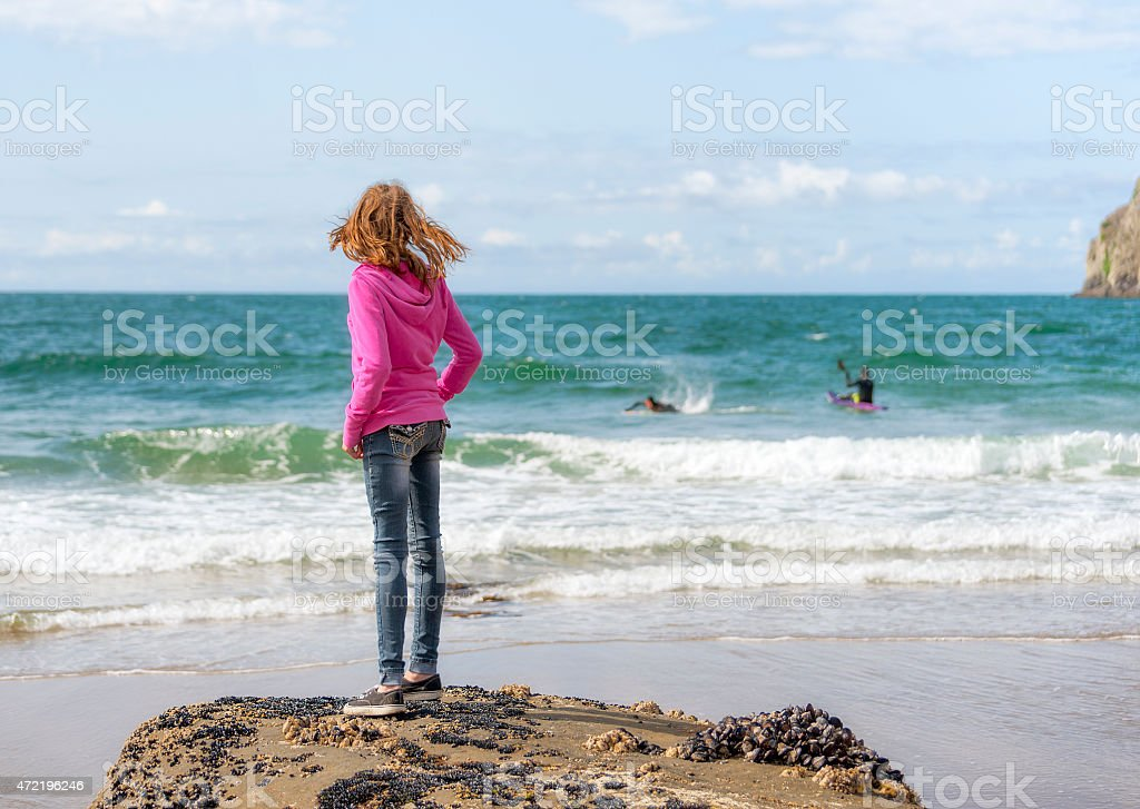 Girl in hoodie looks out at surfers at Pacific City stock photo