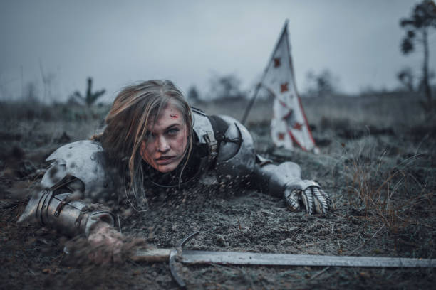 girl in image of jeanne d'arc in armor crawls in mud with sword in her hands on background of flag. - battle stock photos and pictures
