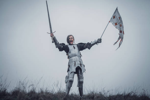 girl in image of jeanne d'arc stands in armor and issues battle cry with sword raised up and flag in her hands. - indumento corazzato foto e immagini stock