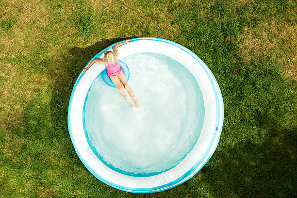 girl in inflatable swimming pool, summer day on dried grass - inflatable ring bildbanksfoton och bilder
