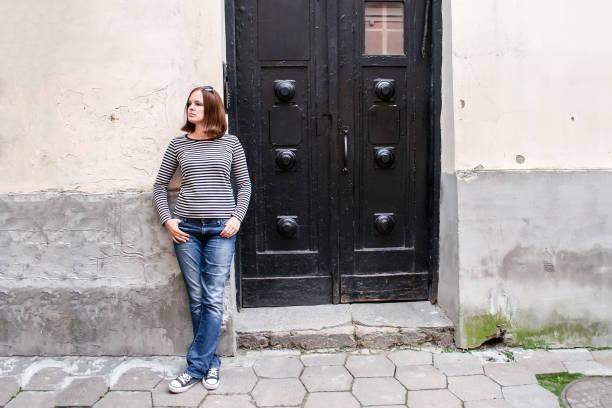 Une fille en jeans, un pull rayé et baskets est debout près de la porte noire en bois d'une vieille maison et regarde sur le côté - Photo