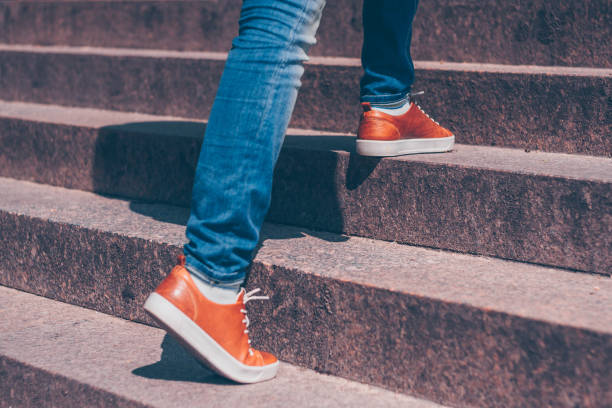 a girl in jeans and beautiful leather shoes steps over the marble steps of the staircase - staircase stock photos and pictures