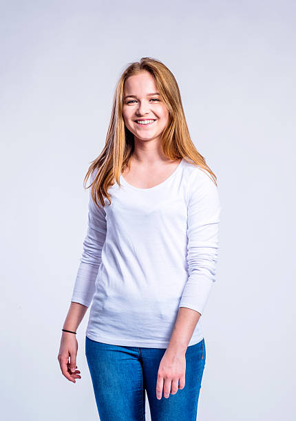 Girl in jeans and t-shirt, young woman, studio shot Teenage girl in jeans and white long sleevedt-shirt, young woman, studio shot on gray background long sleeved stock pictures, royalty-free photos & images