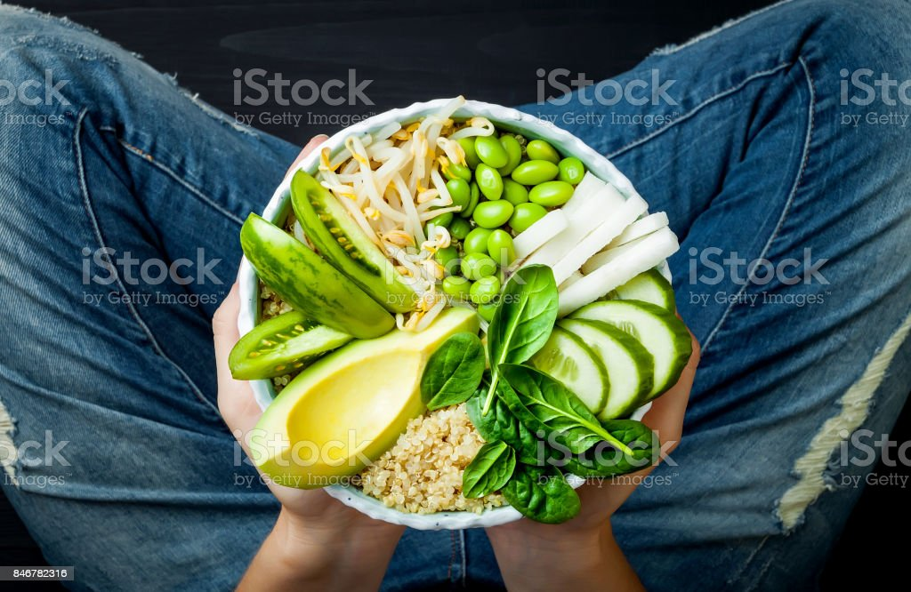 Girl in jeans holding vegan, detox green Buddha bowl with quinoa, avocado, cucumber, spinach, tomatoes, mung bean sprouts, edamame beans, daikon radish. Top view, overhead stock photo