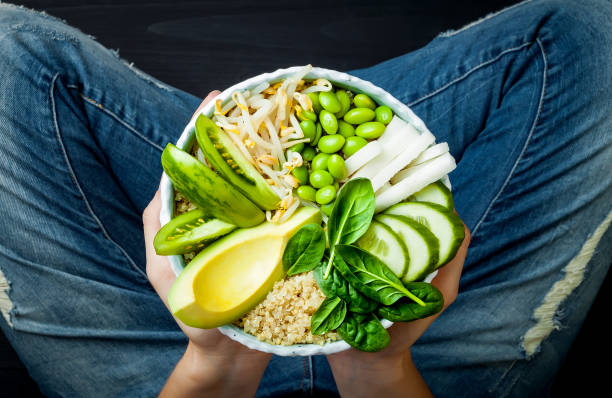 girl in jeans holding vegan, detox green buddha bowl with quinoa, avocado, cucumber, spinach, tomatoes, mung bean sprouts, edamame beans, daikon radish. top view, overhead - vegetarian stock photos and pictures