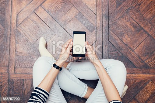 istock Girl in jeans sitting on the floor at home and using a mobile phone 668297200